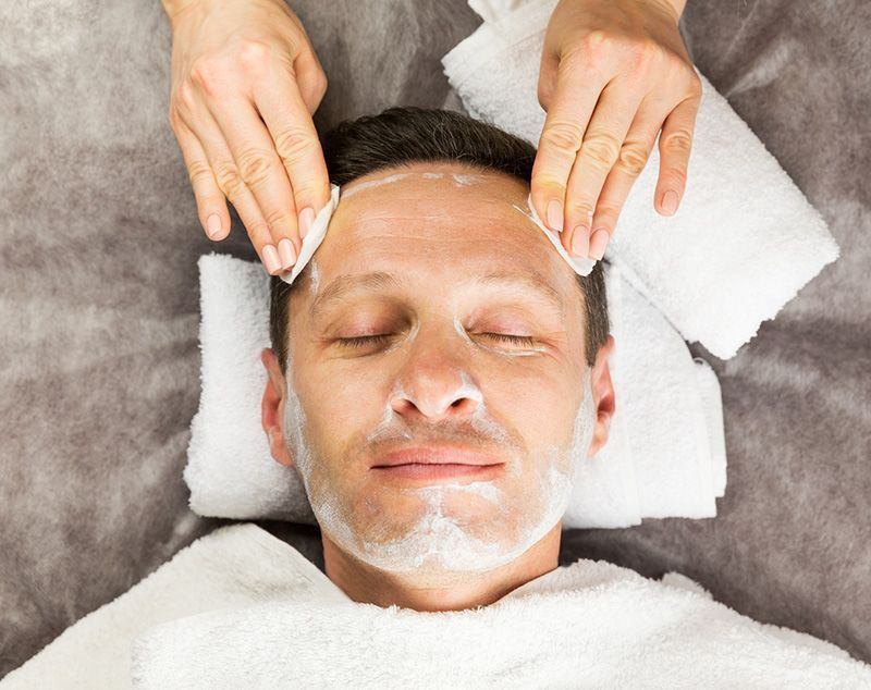Male face with cream mask, hands of professional cosmetologist with cotton sponges