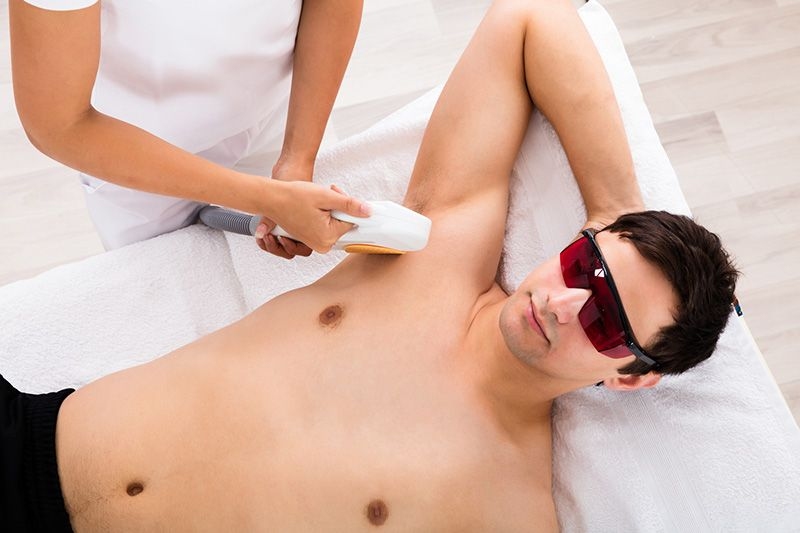 High Angle View Of A Therapist Giving Laser Epilation Treatment On Man's Armpit